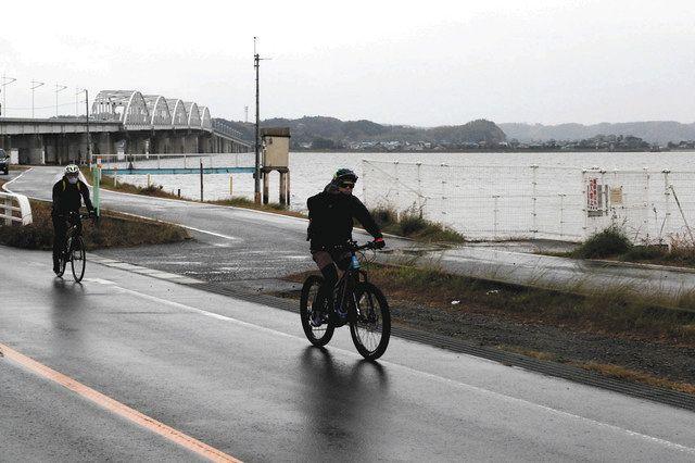 北浦沿いを自転車で走るモニター参加者=行方市で