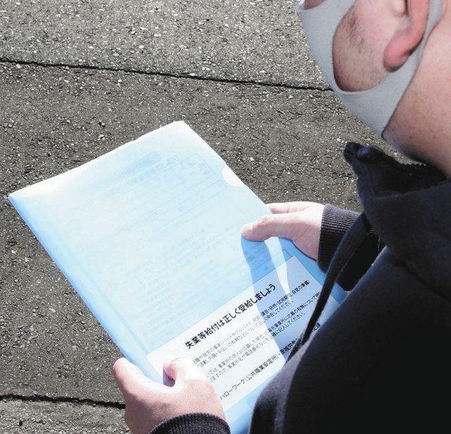 新型コロナウイルスの影響で解雇され、ハローワークで受け取った資料を見つめる男性=水戸市で