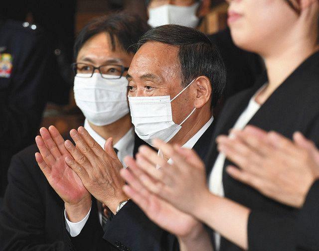 首相官邸を去る安倍首相を拍手で見送る菅官房長官(中央)