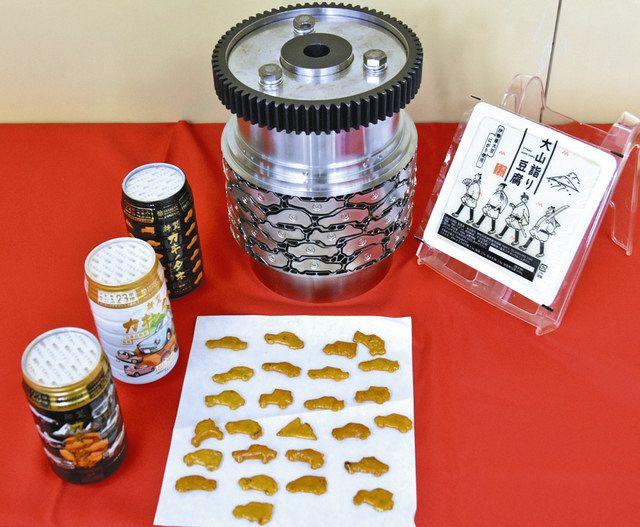 車の形をした「新型カキノタネ」(中央手前)と製造するための金型(同奥)、「大山詣り豆腐」(右)