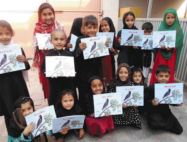 シャンティ国際ボランティア会が出版した絵本をもらって喜ぶアフガニスタンの子どもたち=2018年撮影、同会提供