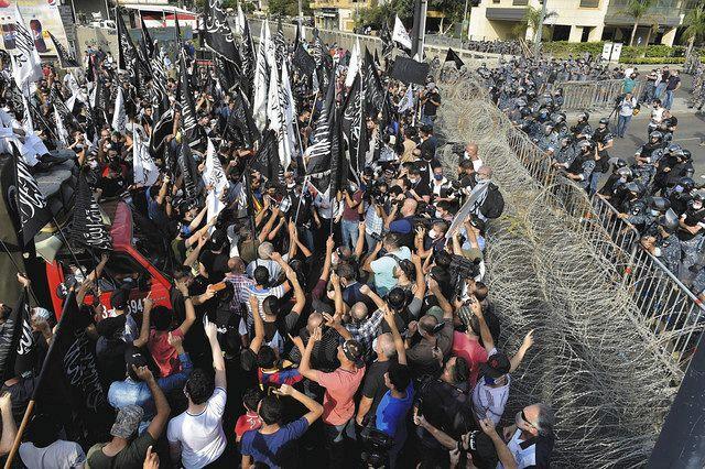 10月30日、レバノンの首都ベイルートで、フランス大使館に迫るデモ隊を警戒する治安部隊=ゲッティ・共同
