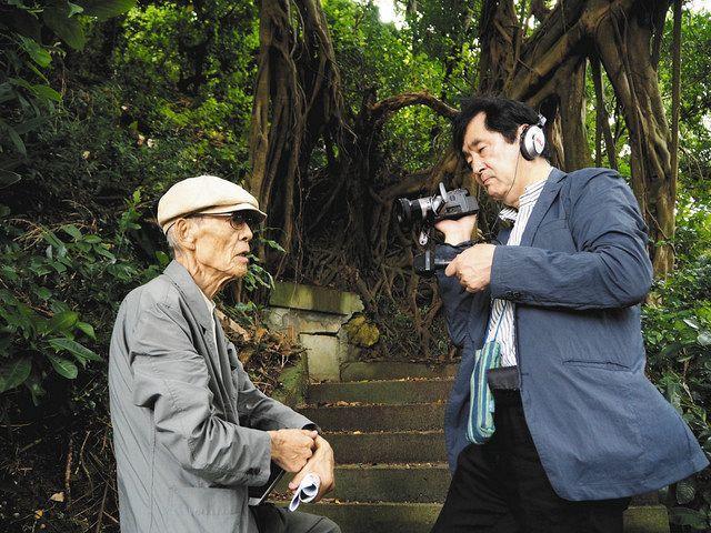 沖縄戦について語る森口さん(左)を撮影する永田さん=2019年5月撮影