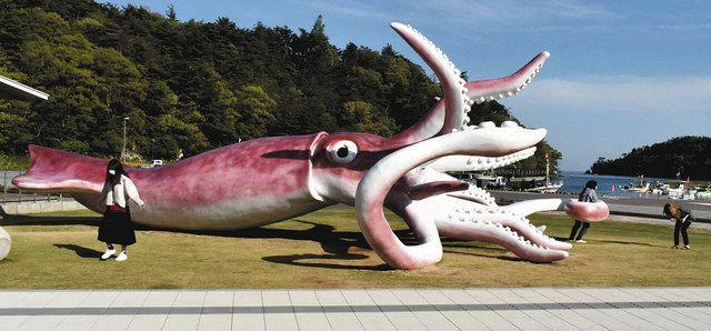イカの駅つくモールに設置され観光客らが写真撮影などをする巨大なイカのモニュメント=6日、石川県能登町越坂で