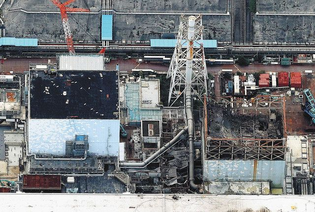 事故発生当初のベントで高濃度に汚染された配管の撤去に向け、準備が進む現場は、水素爆発で最上階が大破した1号機(右側)と爆発を逃れた2号機の間にある=2021年10月11日、福島県大熊町で、本社ヘリ「おおづる」から