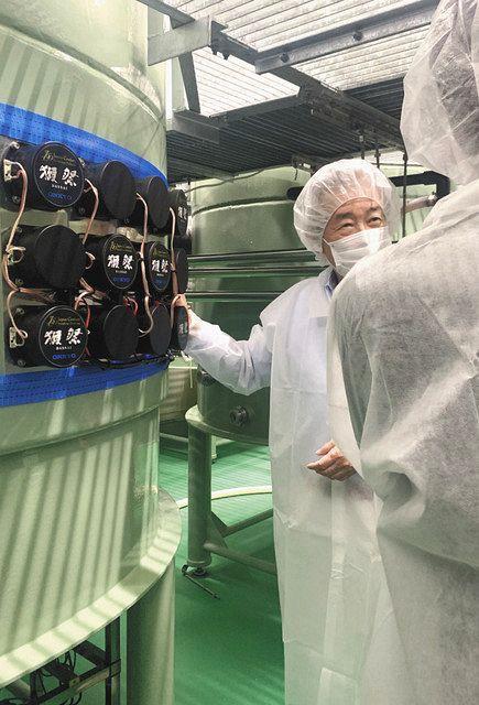 A tank containing moromi with symphony = provided by Asahi Shuzo