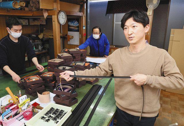 伸縮性のあるベルトを手に、新成人への思いを語る長沢猛臣社長(右)