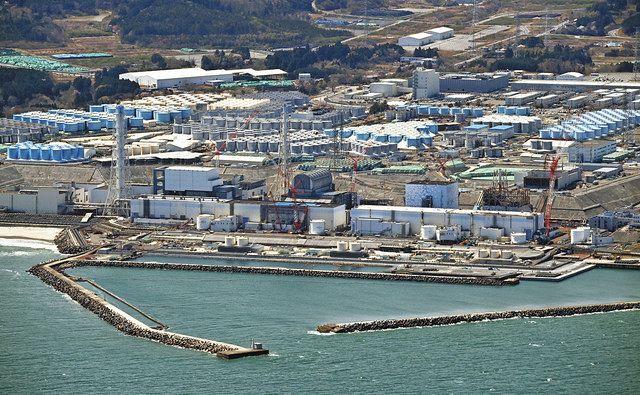 事故収束作業が進む福島第一原発の原子炉建屋。奥には処理水のタンクが並ぶ=10日、福島県で、本社ヘリ「おおづる」から(戸田泰雅撮影)