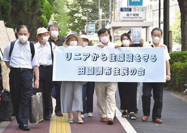 横断幕を手に東京地裁に向かう原告団=19日午前、東京・霞が関で