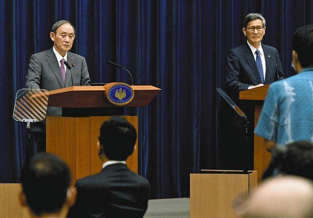 記者会見する菅首相。右は政府の感染症対策分科会の尾身茂会長