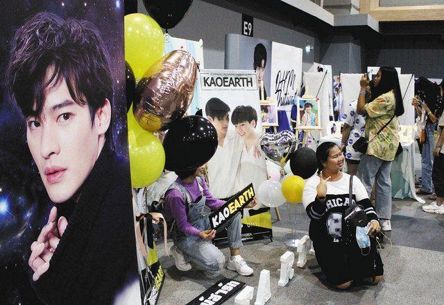 BLドラマのイベント会場で、お気に入りの俳優のパネルと記念写真に収まるファンたち=バンコクで