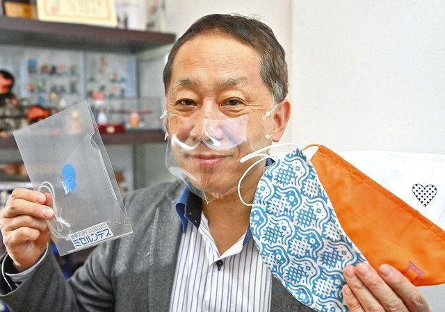 透明マスク「ミセルンデス」をつける東京和晒の滝沢一郎社長。左手に持つのは手ぬぐい用生地でつくった「らくなマスク」など