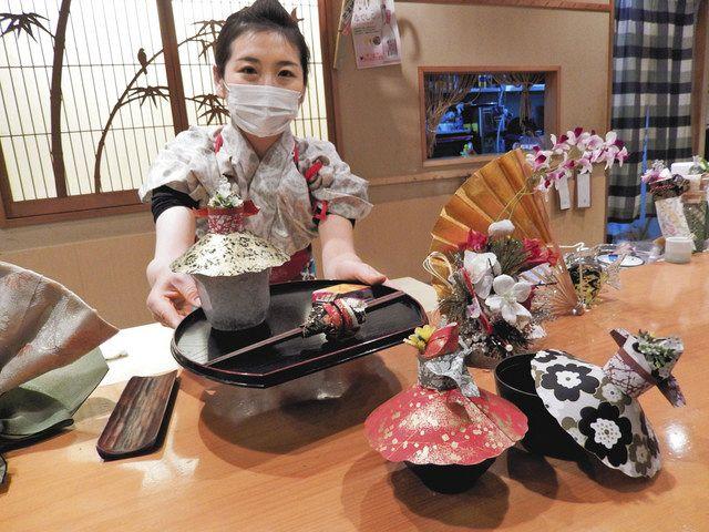 「どうぞ」と盆を差し出す、なでしこ寿司店長の千津井さん。わんにかぶせているのが、飛沫対策になる和紙人形「華姫」=千代田区で
