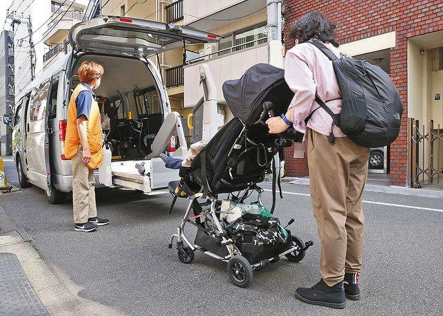 放課後デイの送迎車に子供用車いすのまま乗りこむ医療的ケア児の息子を送り出すAさん(右)=一部画像処理