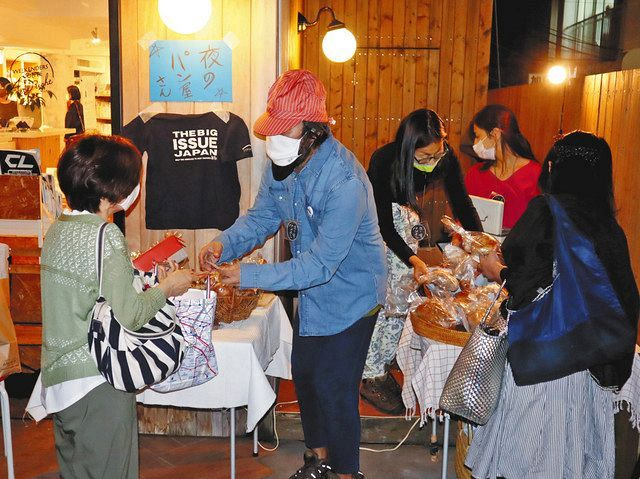 都内のパン店から集めたパンを売るホームレスの男性(中央)=新宿区で
