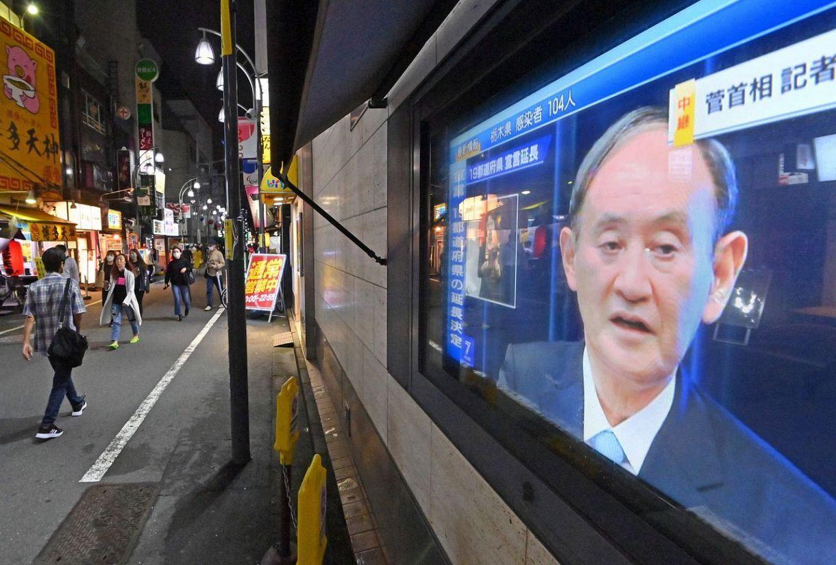 9日、東京・新橋の繁華街で菅首相の自民党総裁選不出馬の理由や、緊急事態宣言の延長について伝える街頭テレビ