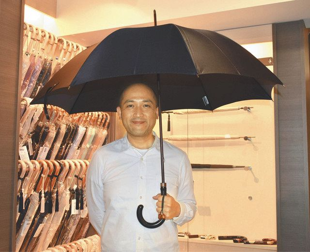 社内で、トトロの雨傘を手にする前原慎史社長=台東区で
