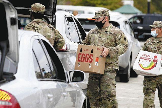 20日、米南部テキサス州ダラス郊外で、車で待つ人たちに食料を配る兵士ら=AP