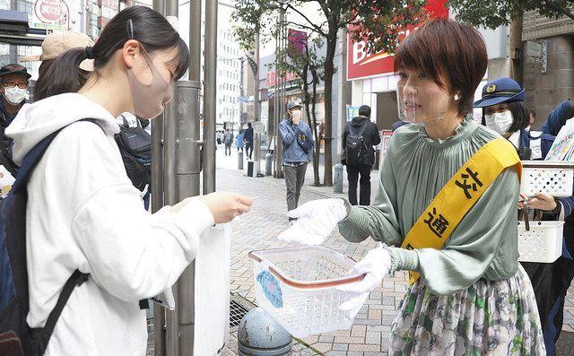 警視庁の交通安全イベントでアサガオの種を配る高田香さん(右)=6日、東京都千代田区で(市川和宏撮影)