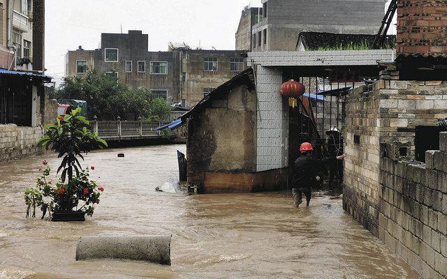 先月24日、中国貴州省恵水県で、大雨のために冠水した住宅地=AP